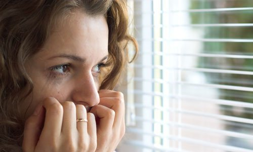 scared-woman-looking-out-window-500.1